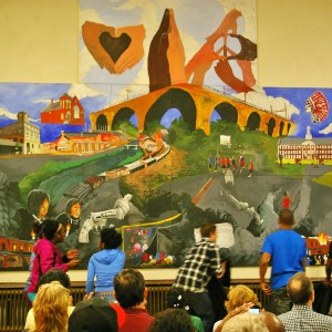 Students pull down the curtain to reveal their finished mural. The painting was designed and painted by Bridge Academy students with help from the Art Partners Studio.