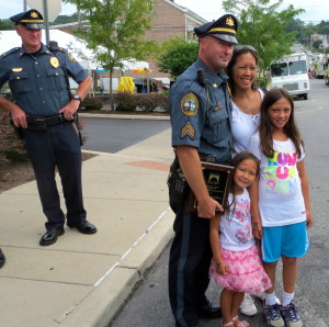 As Coatesville Police Chief Jack Laufer (left) looks on, Sgt. Rodger Ollis Jr. poses with his wife, Michele, and daughters