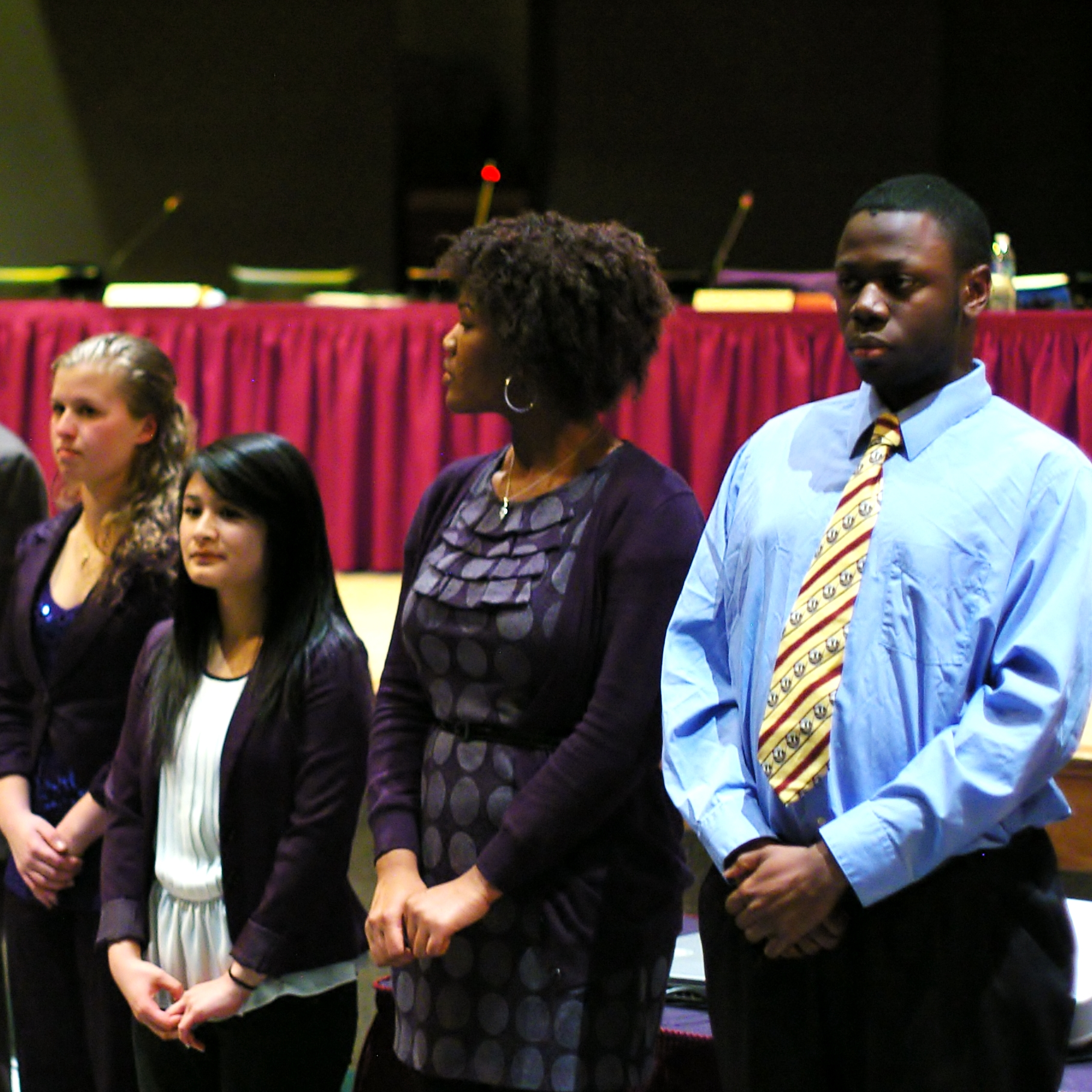 (left to right) Nicolina Sciarretta, Johnna Morales, Gabrielle Hines, and Joshua Mensah stand before the audience as Mr. Fisher recognizes them as some of the top students in their class.