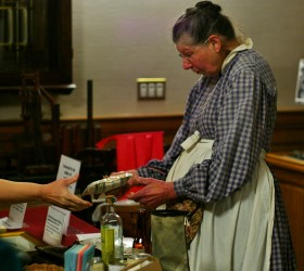 Dr. Florence K. Williams presents recreated artifacts to attendees. Items included slippers, a brandy bottle, faurina packets, and lemonade mix, which used the same recipe still used today.