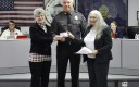 Mary Coine (left) and commissioner Lorraine Tindaro (right) present a check to Police Chief Joseph Elias (middle) for the police department's participation in DARE.