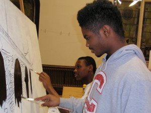 Dondre Pittman (left), 15, and Nasir Newton, 15, work on the image of Coatesville's railroad bridge.