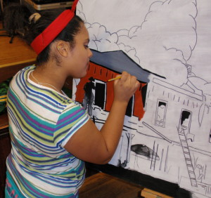Amanda Gayton, 15, works on a section of the mural depicted the arsons that terrorized Coatesville.