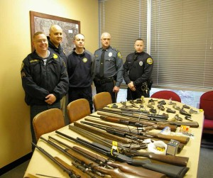 Police officers stand next to the guns collected during Saturday's gun buyback. The department collected 38 guns, a combination of shotguns, rifles, pistols, and ammunition. The department hopes that the collection will reduce the number of firearms available to potential criminals as well as reducing the number of crimes related to acquiring those guns.
