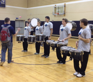 Unionville High Drumline Coach Cody Stafford (left) gives his musicians instruction before a recent performance.