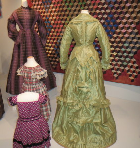 Two women's dresses, a green striped silk and a purple and black plaid silk taffeta, and two child's dresses, a red, black and white plaid cotton and a magenta, black and white plaid wool trimmed in black velvet, were worn in Chester County in the 1860s and 1870s.