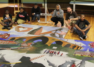 Some of the creators of the Darkness to Light mural surround the five panels after their completion.