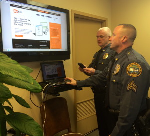 Coatesville Police Chief Jack Laufer (left) and Sgt. Rodger Ollis demonstrate the ease with which citizens can contact police anonymously through a phone app.
