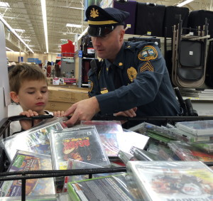 Sgt. Rodger Ollis helps his shopper with a DVD selection.