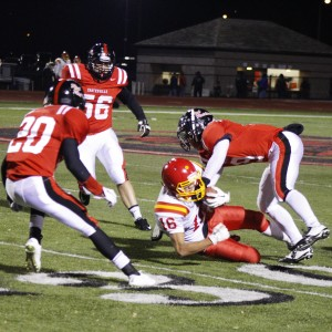Coatesville's defense swarms the running back in the backfield.