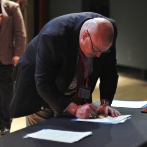 Dean Snyder signs the ratification acknowledging district progress in following the plans laid out by a host of human rights organizations.