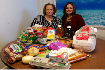 Mrs. Hackmeister and Mrs. Knecht seated in front of donated items for one family""